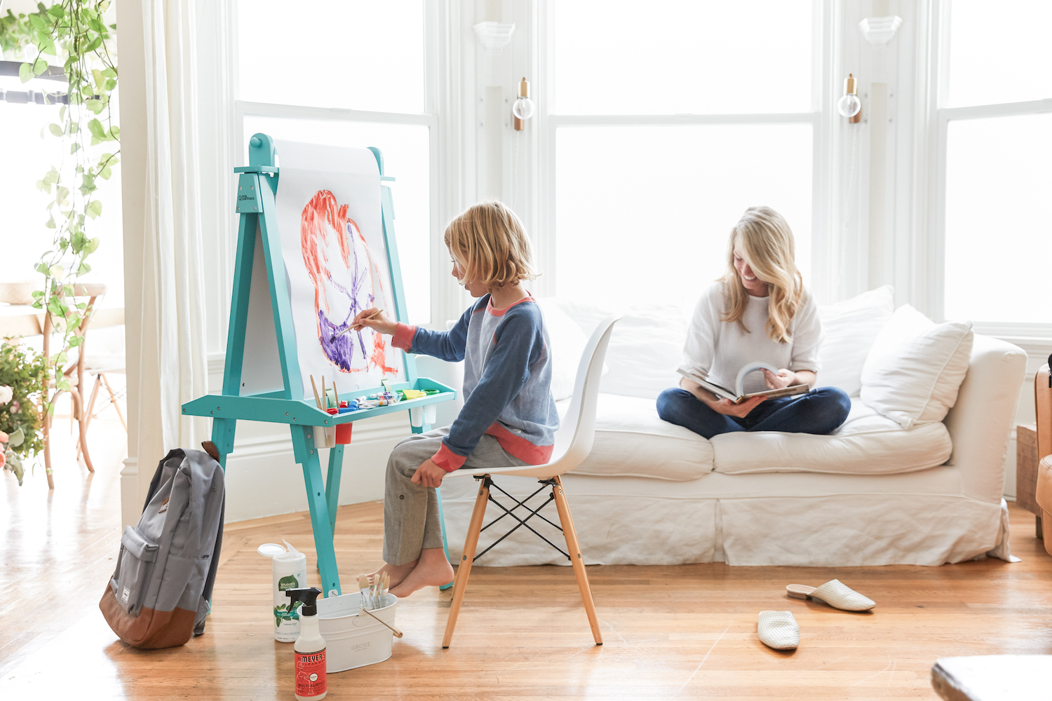 child painting at an easel while mom reads on white couch nearby