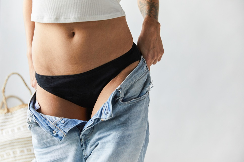 woman putting jeans on over period underwear