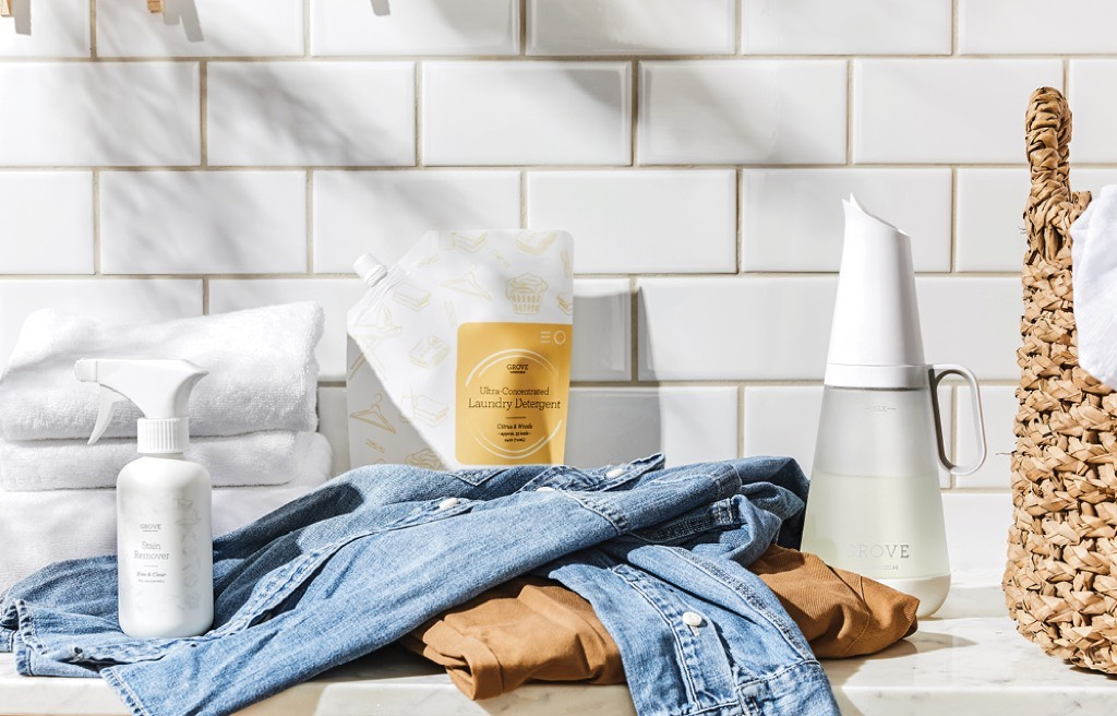 Natural laundry detergents and oil stained jeans on a white counter-top