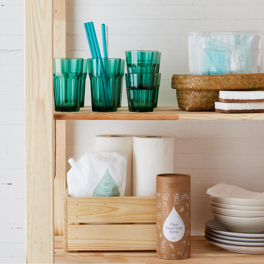 Image of wooden shelf with 3 green cups, one cup holding several green silicone straws
