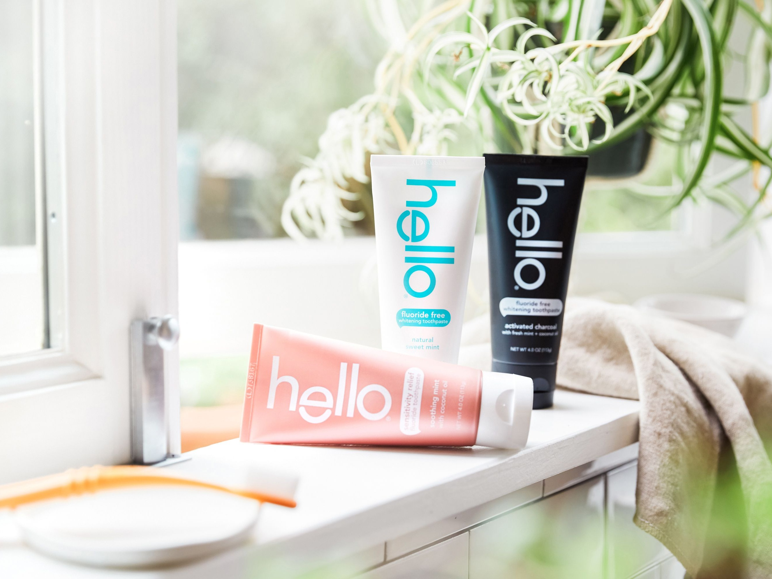 three hello toothpaste tubes on a bathroom counter