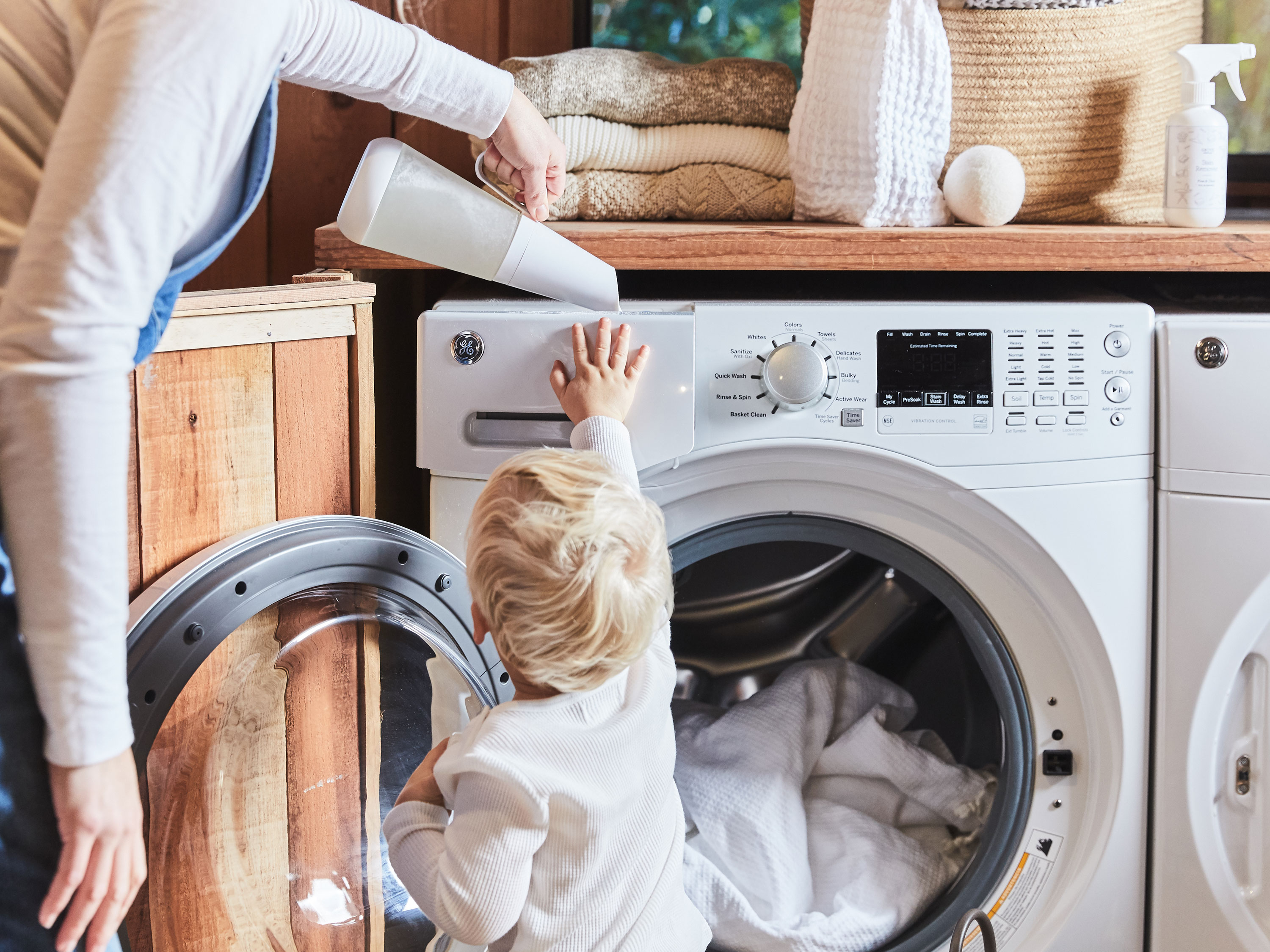 Parent holding child's hand while they watch clothes spin in the dryer