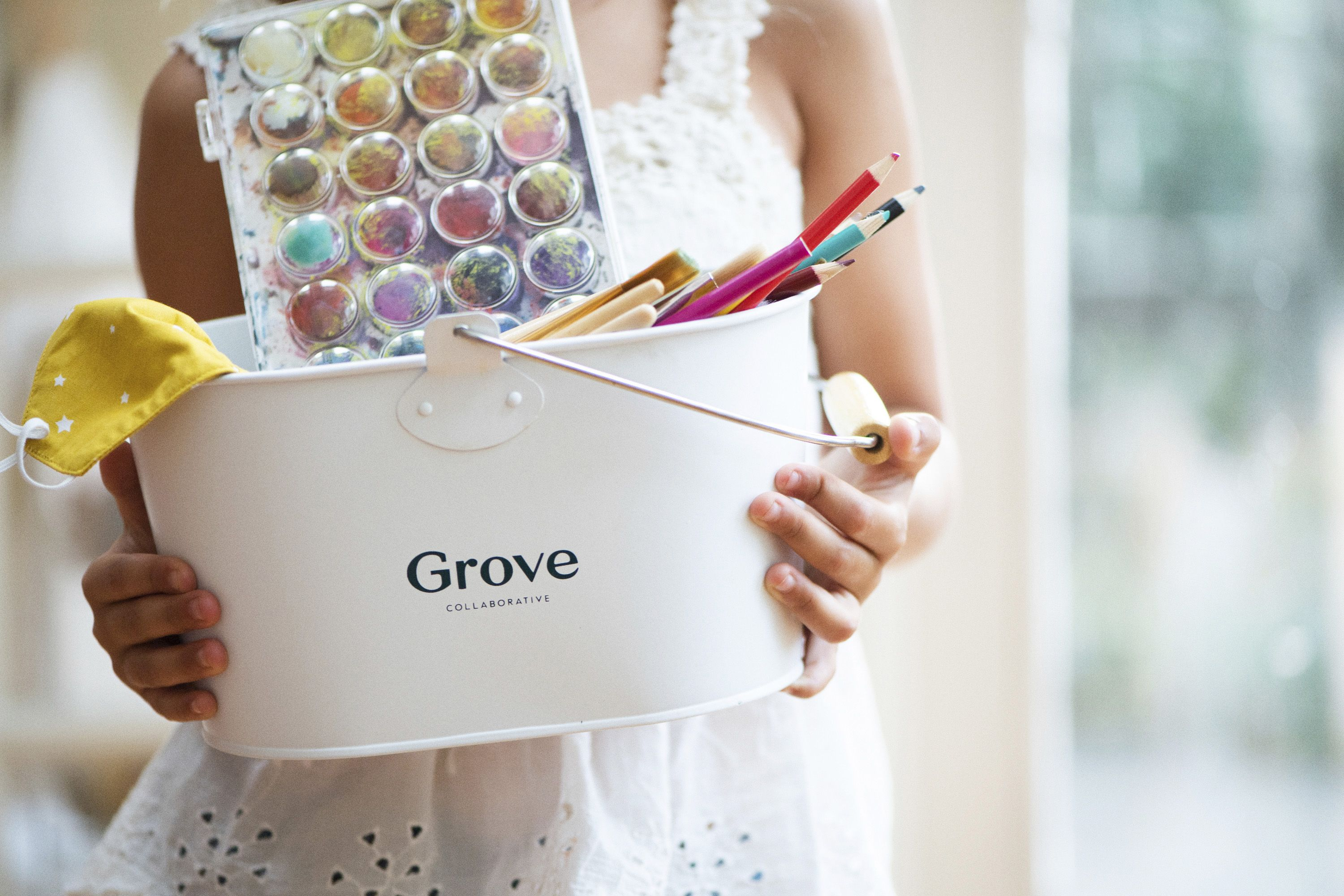 person holding Grove caddy with ink and coloring supplies