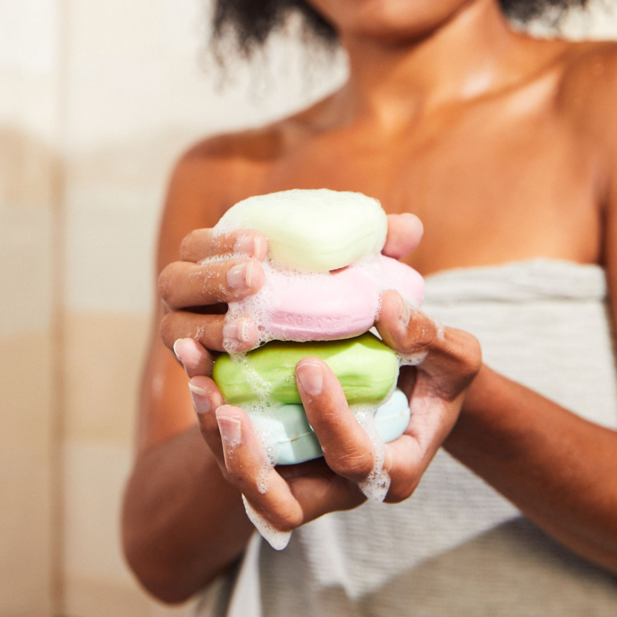 woman holding stack of bar soaps and shampoos