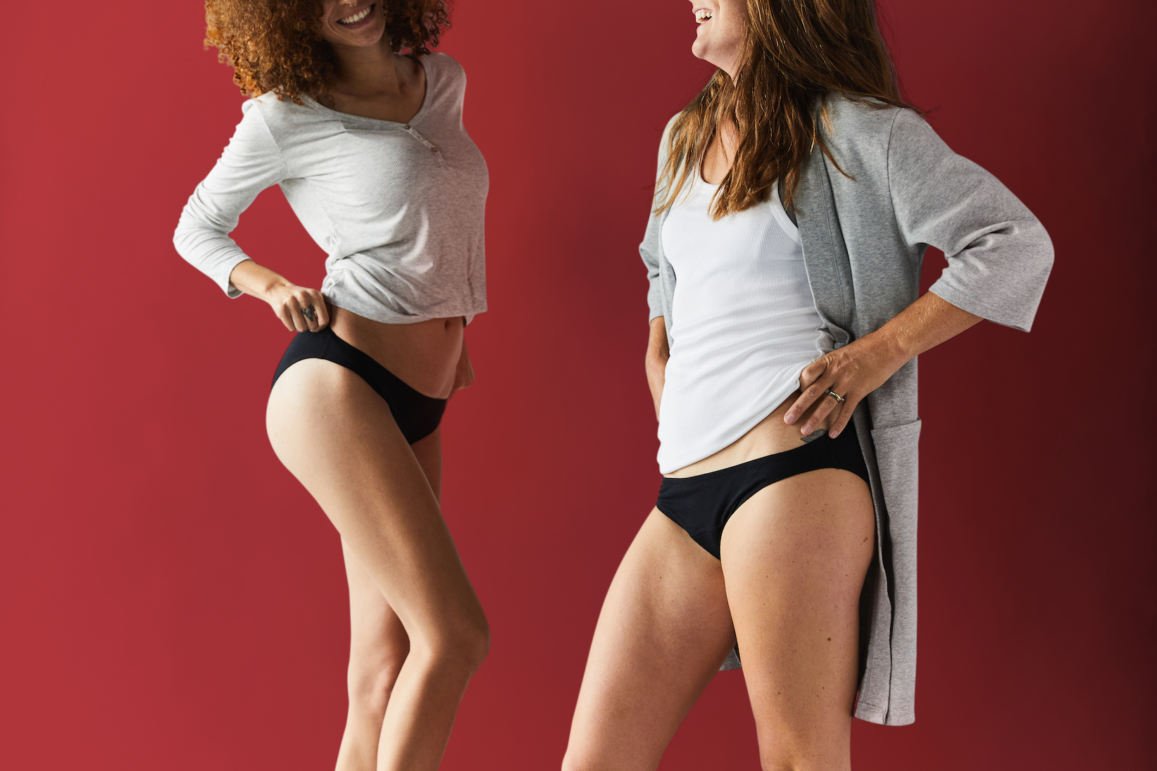 two women in tops and black period underwear against red background
