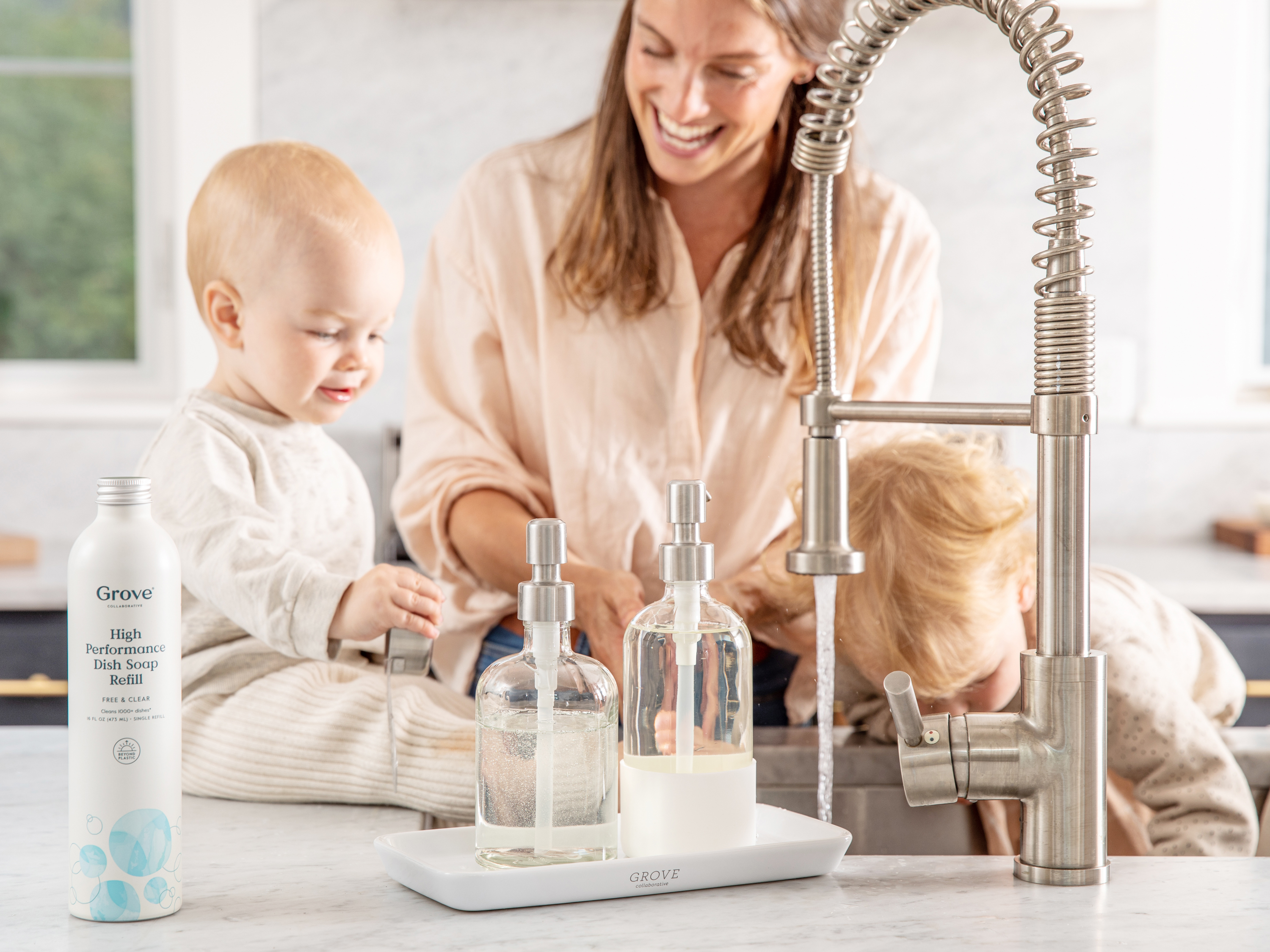 Young adult cleans the brass sink with two young children helping