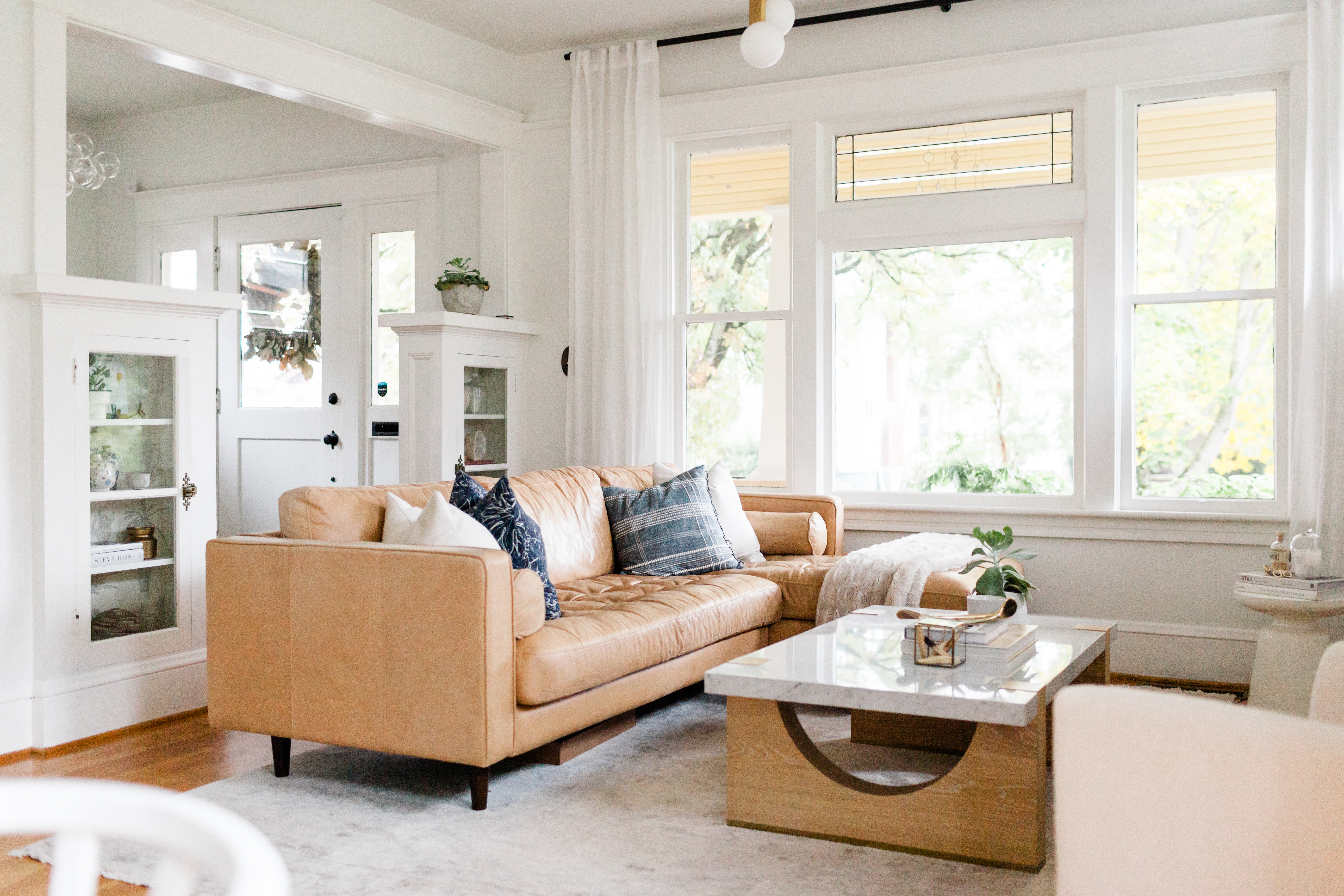 Tan leather couch in a white living room