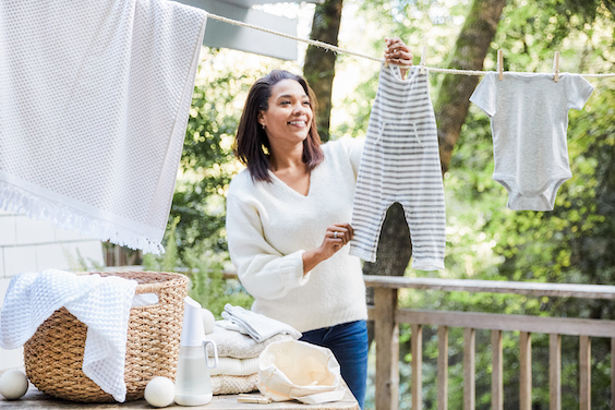 woman hanging baby clothes out to line dry in outdoors