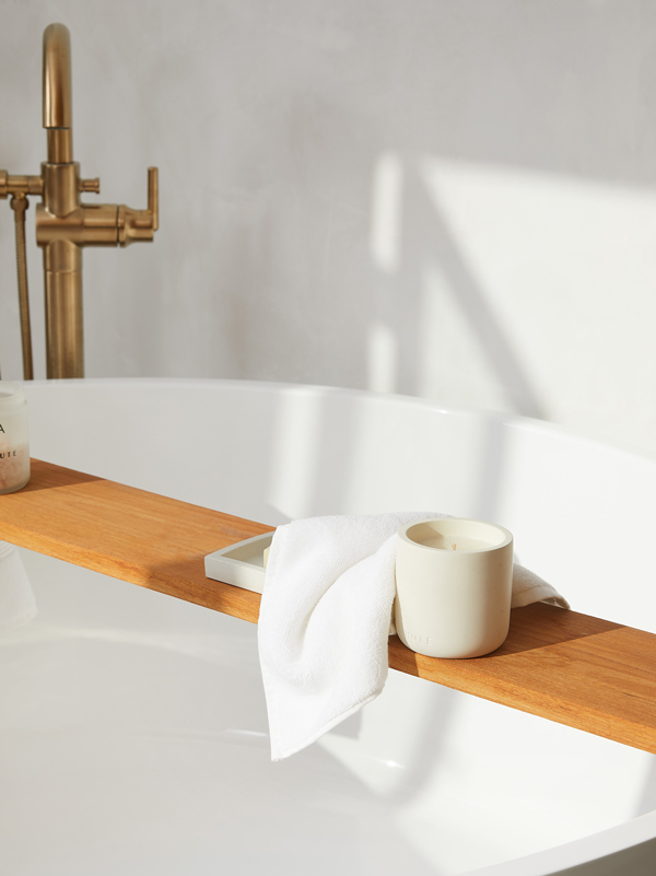 Close up of a white washcloth and a scented towel resting on a bathtub caddy