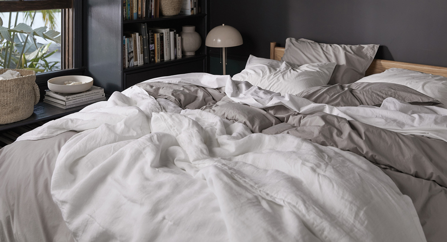 Close up of a bed in a dark colored bedroom with mixed grey and white sheeting.