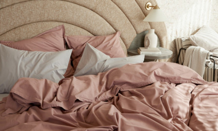 Bedroom with a light brown rounded headboard and messy clay colored percale sheeting.