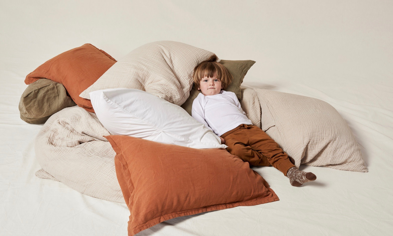 Little boy surrounded by pillows.