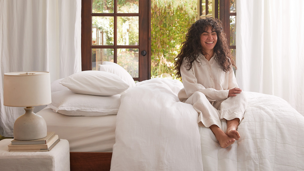 Woman sitting up in bed wearing a Bone colored linen top and pants.