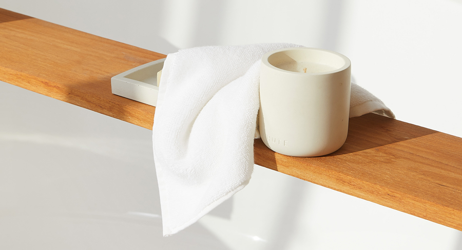 Close up of a white washcloth and scented candle sitting on top of a wooden bath caddy.