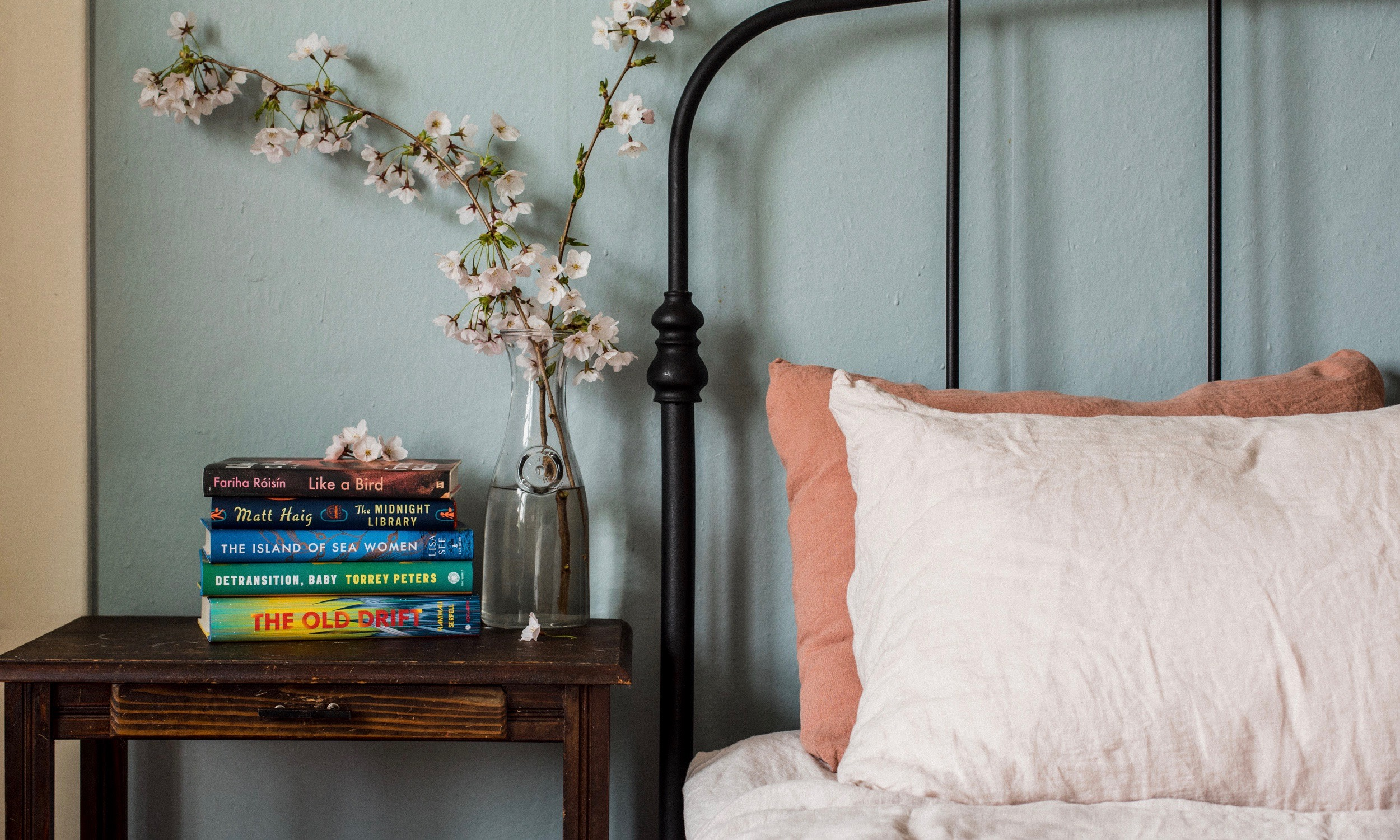 Book stack next to a blush and clay bed.