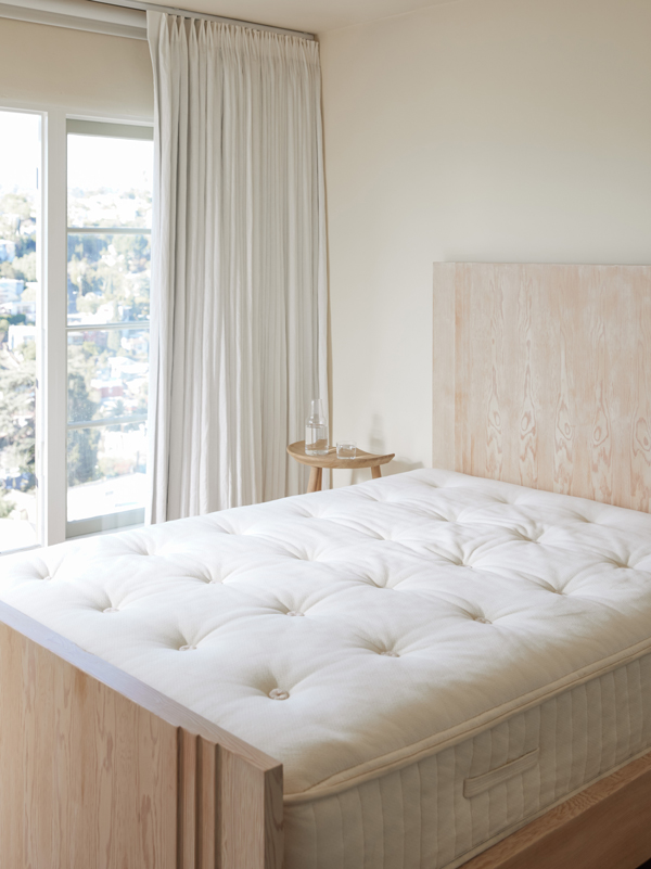 Close up of a bare mattress resting on a bed frame in a bright bedroom.