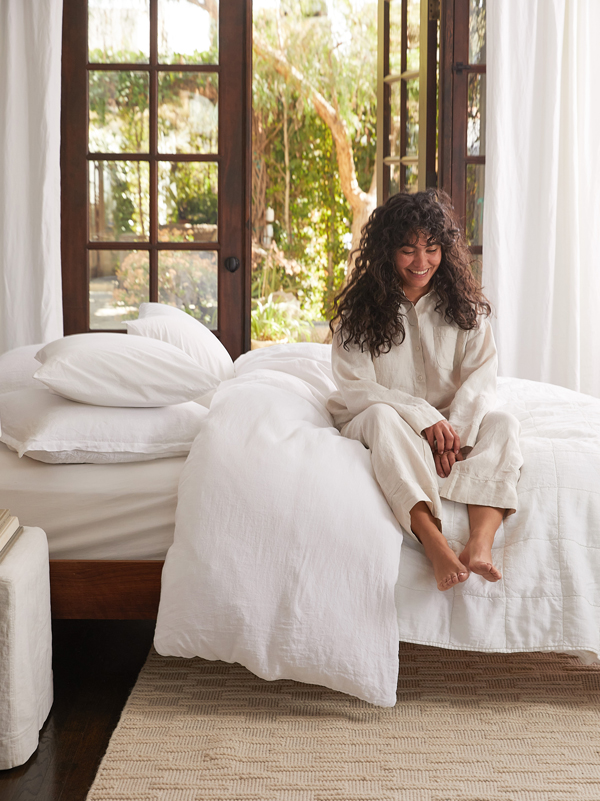Women sitting on a white made bed wearing bone colored linen loungewear top and bottom