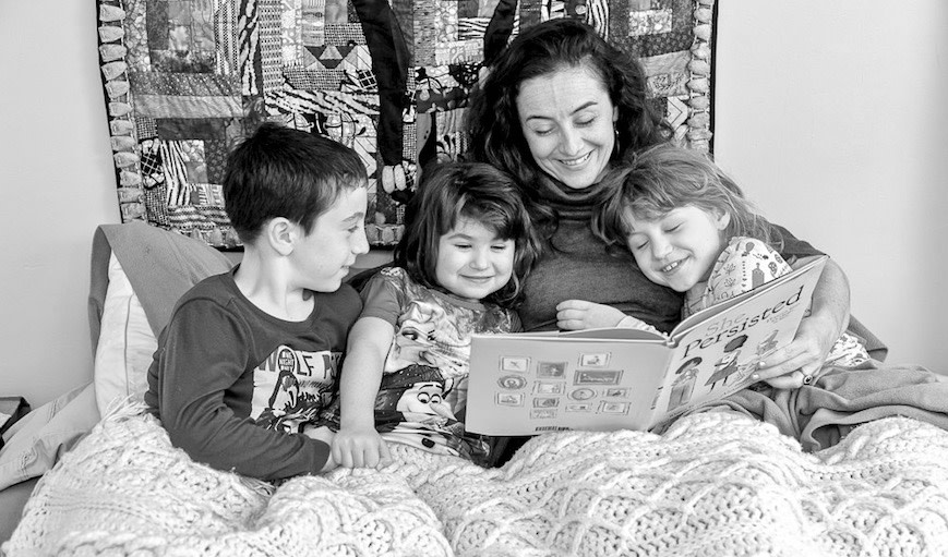 Woman reading to her kids in bed.