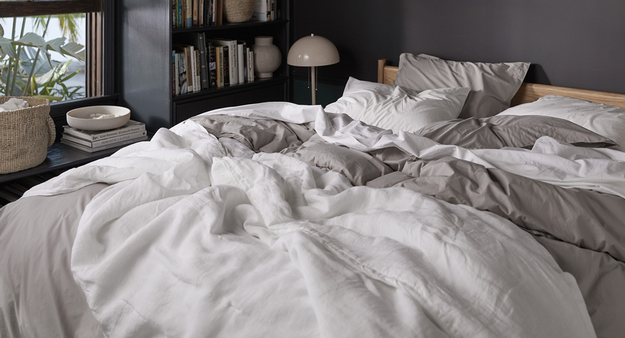 Close up of a messy bed with white and tan bedding against a dark painted bedroom wall.
