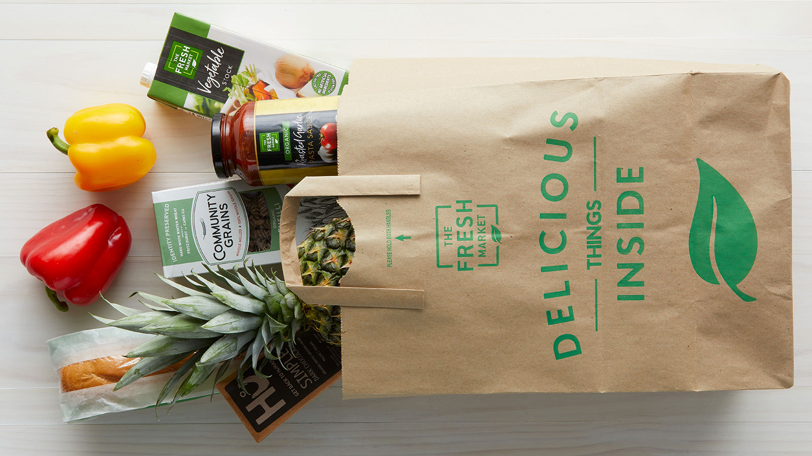 The Fresh Market grocery bag with produce, pasta and sauce.