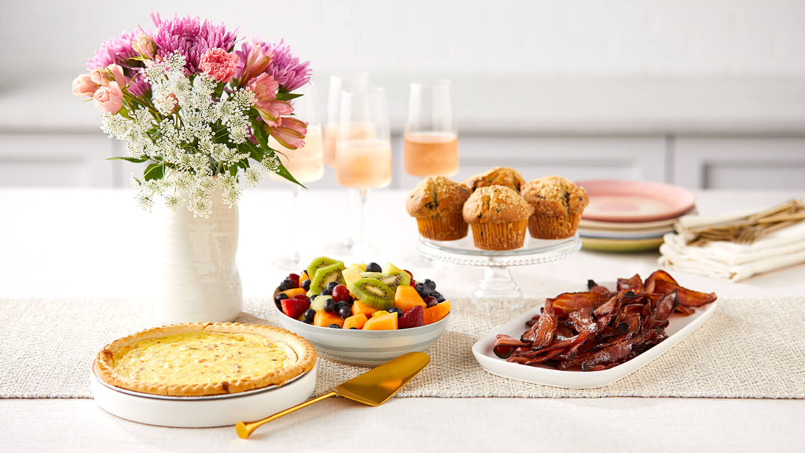 Mother's Day Brunch Meal with quiche, fruit, bacon, muffins and flowers