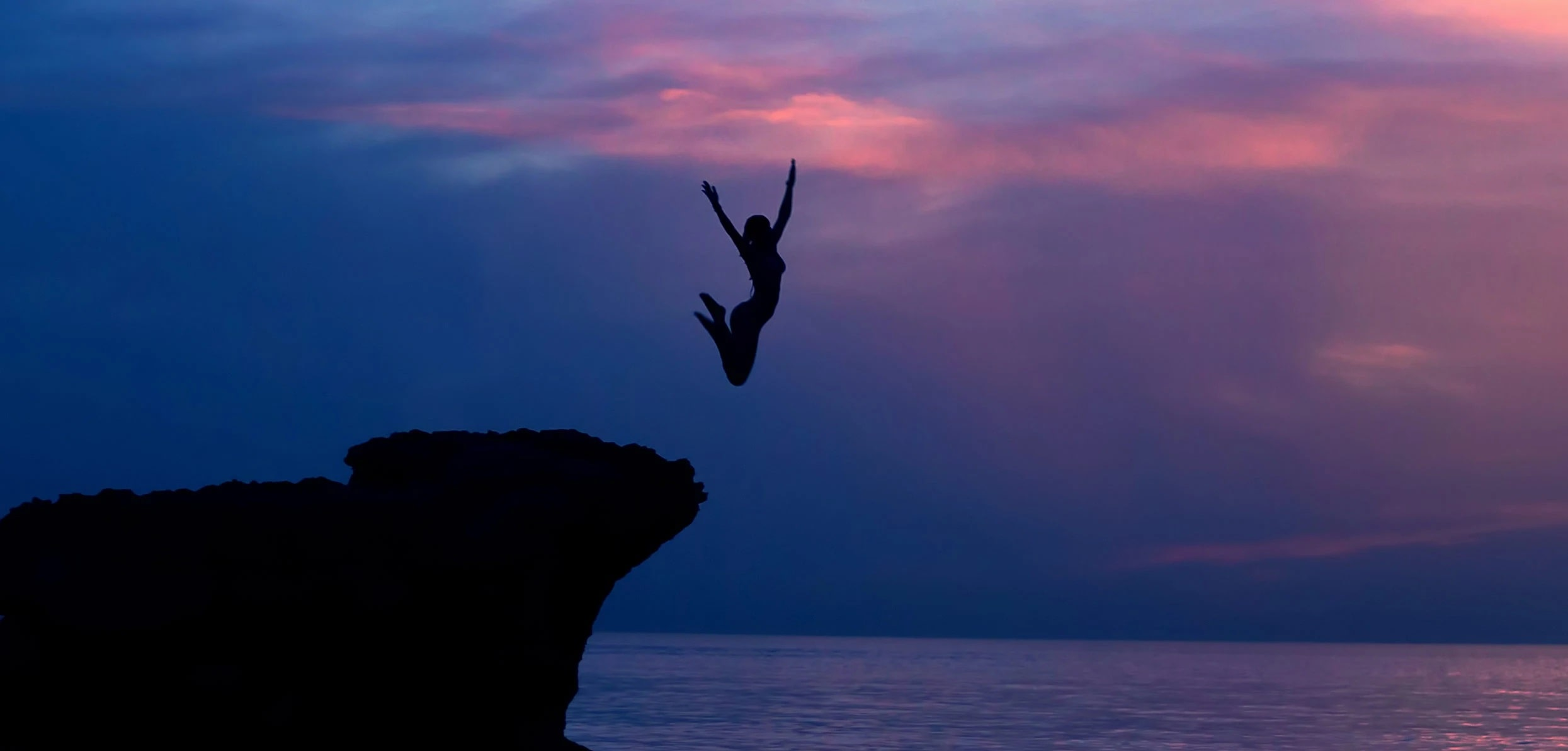 Silhouette of a woman jumping on a cliff - when does menopause start