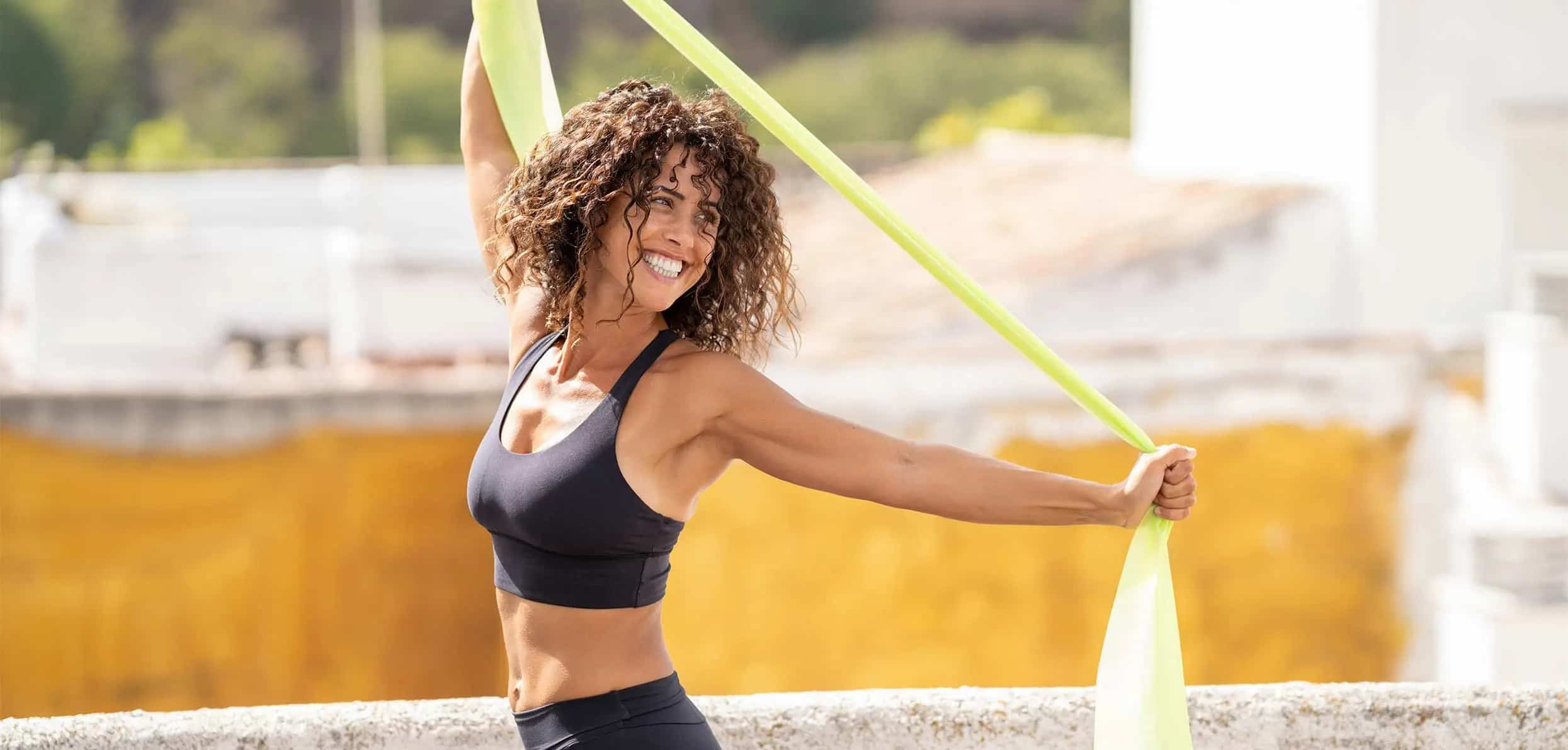 A happy woman happily dancing under the sun - low testosterone treatments