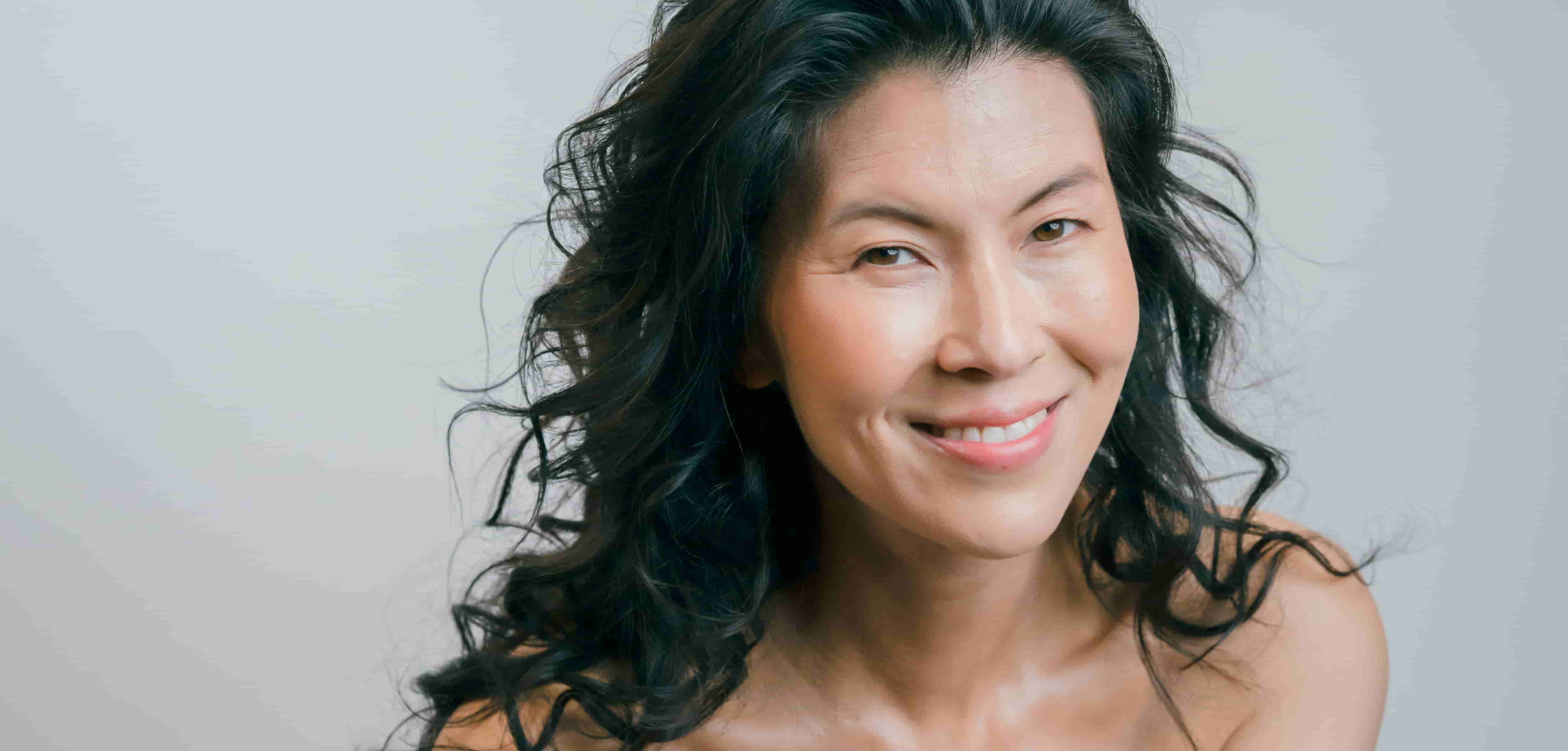 Asian woman with wavy hair happily smiling - feminine dryness remedies