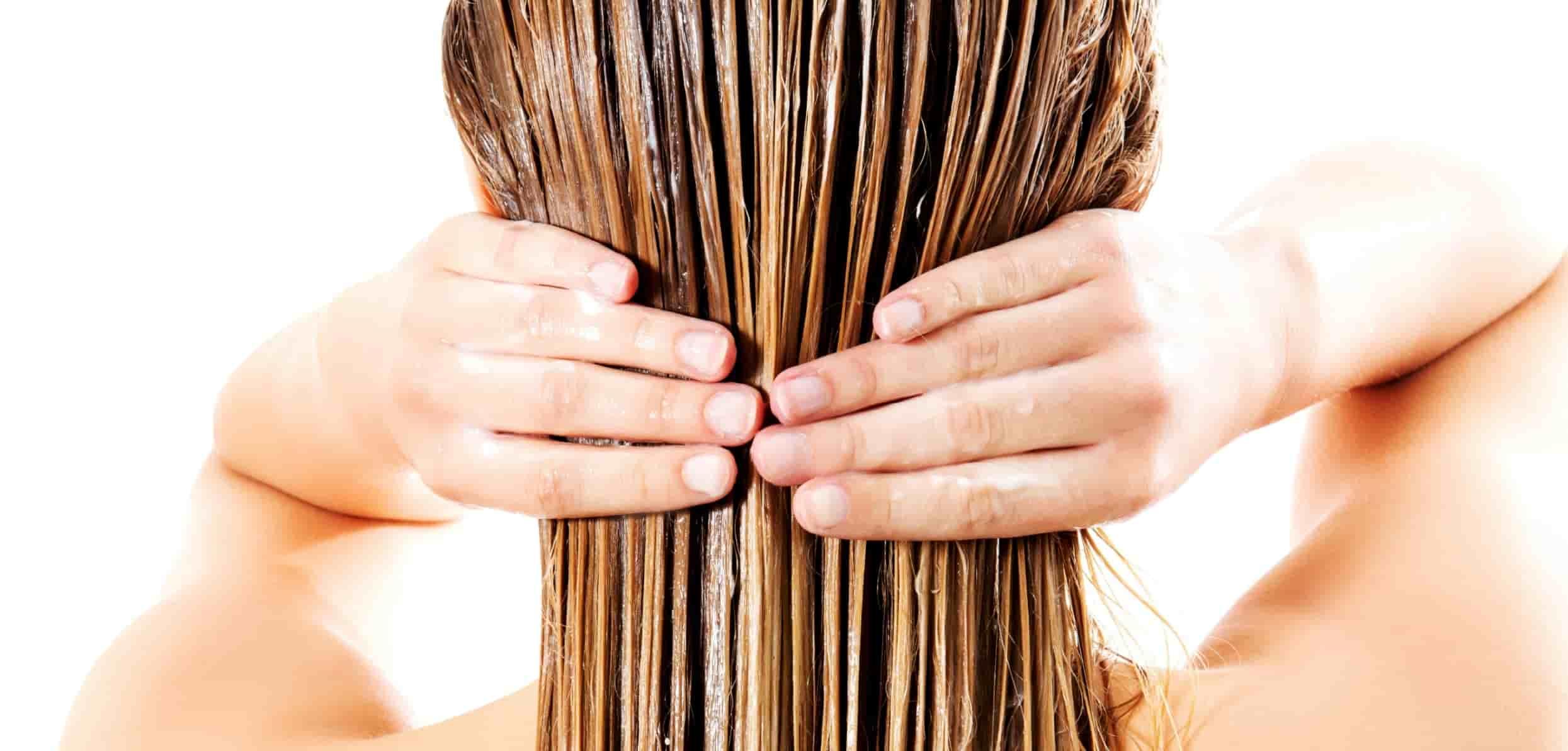Woman applying the treatment on her hair - hair loss and thyroid
