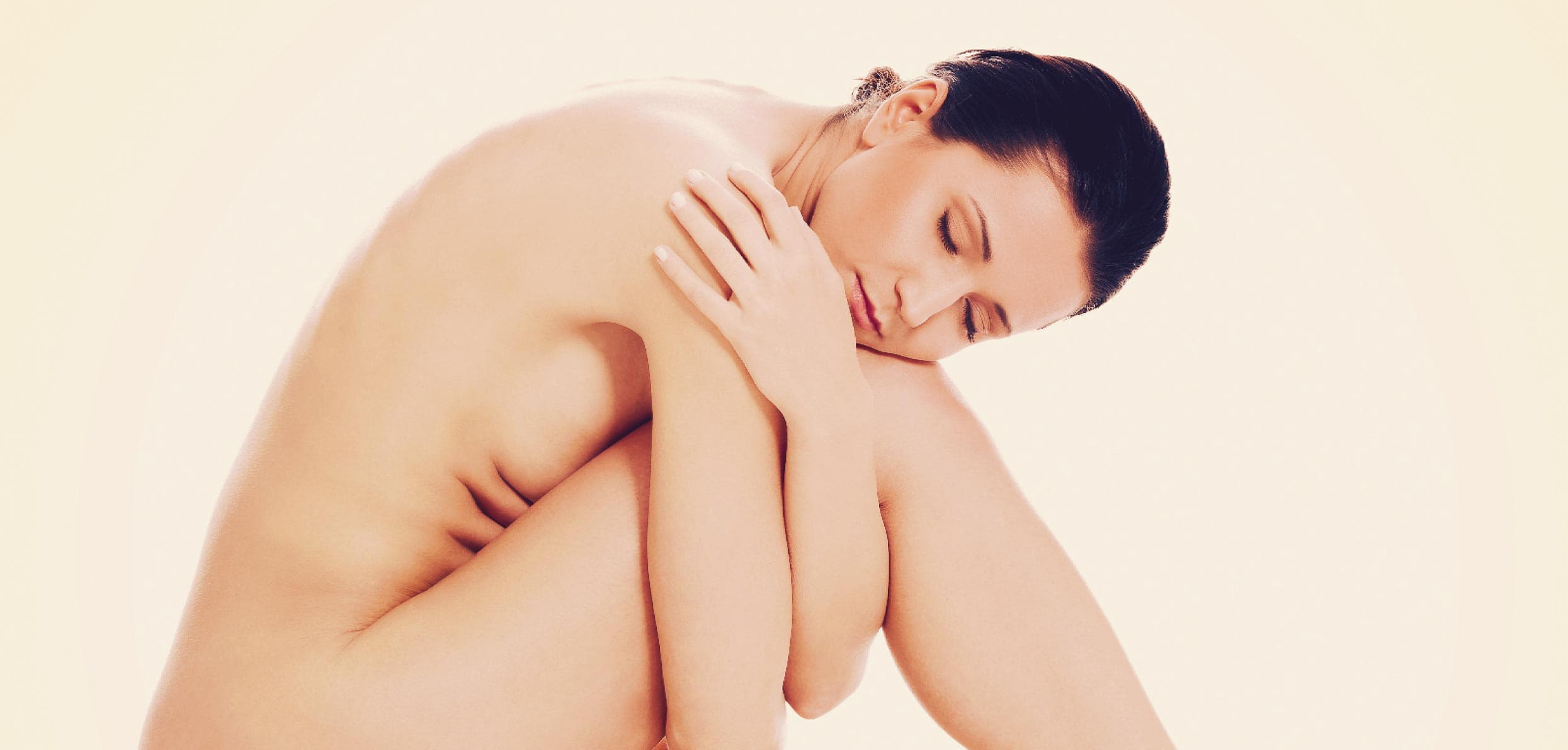 Naked woman sitting in a fetal position while hugging her thighs - prevention of osteoporosis