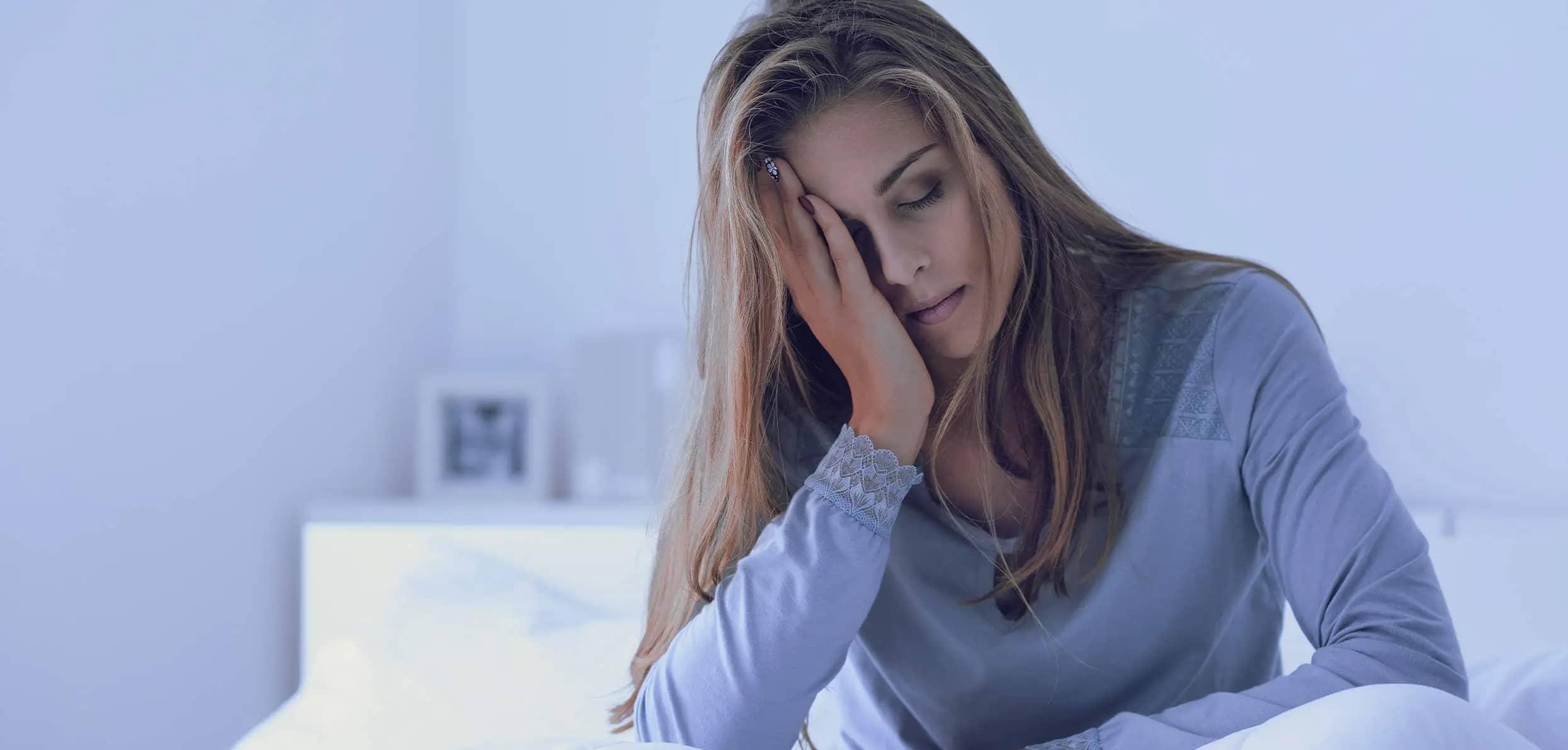 Sleepy woman facepalming - estrogen and sleep disturbances
