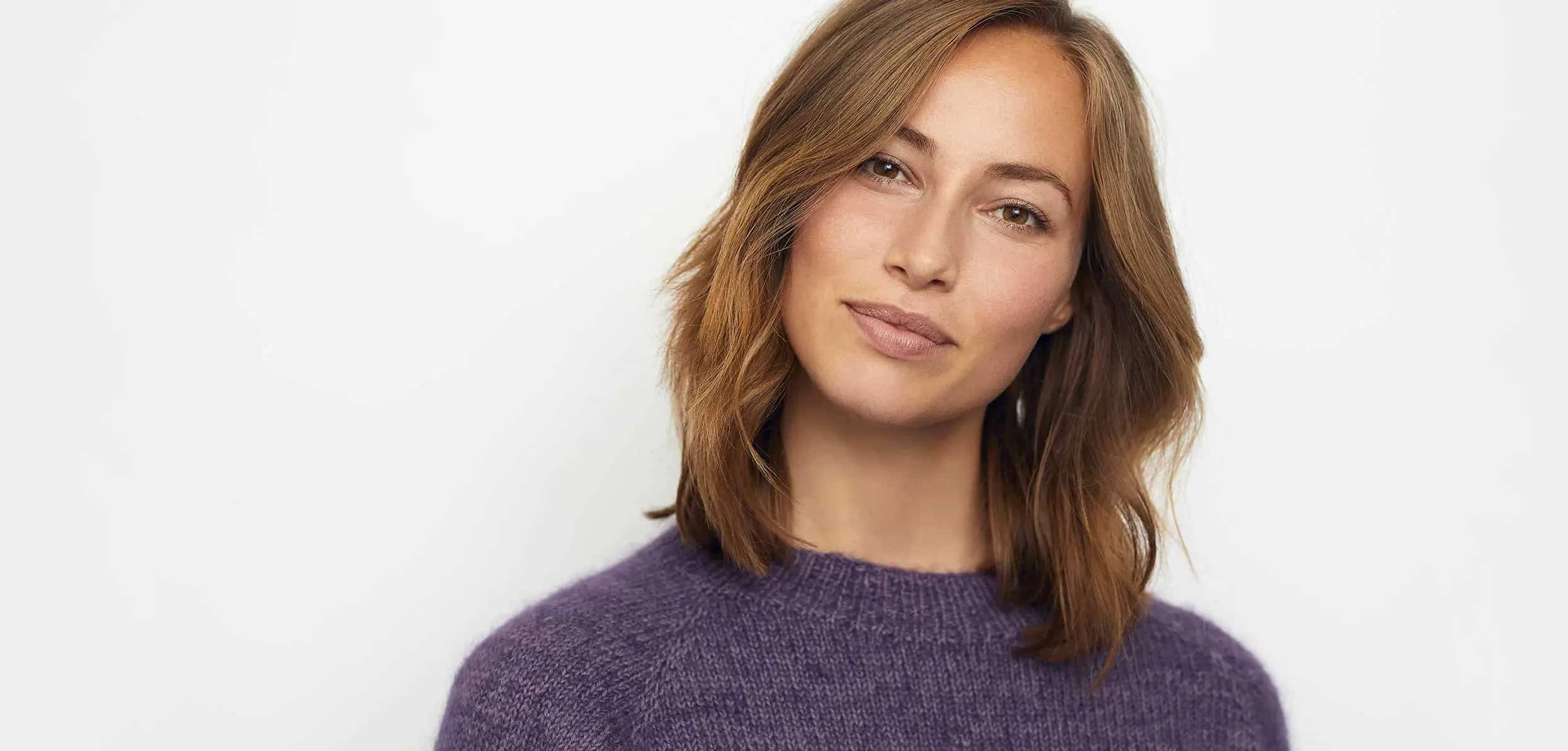 A woman with brown hair and a purple knitted shirt - how hormone replacement therapy works