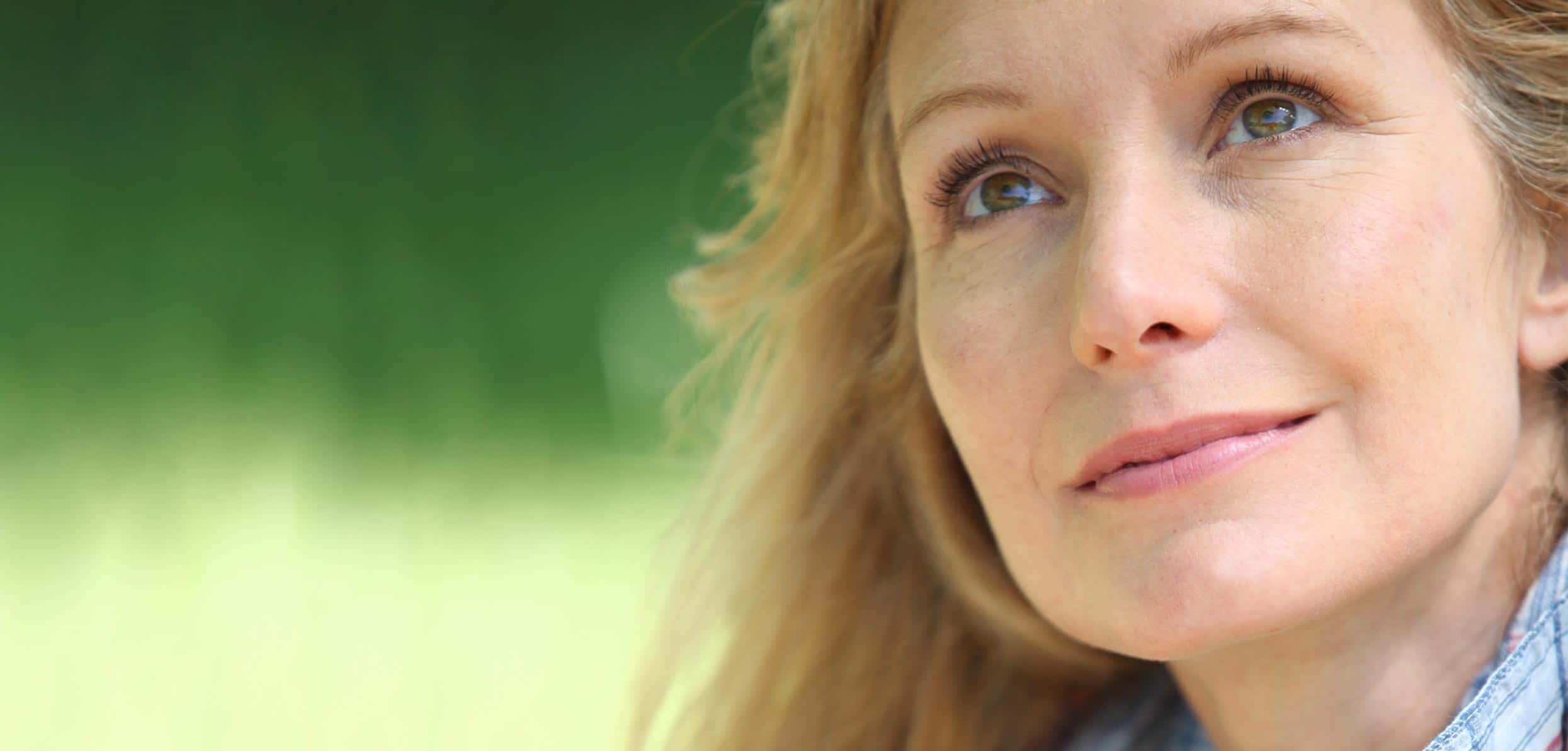 closeup of a woman happily looking upwards - women's health initiative
