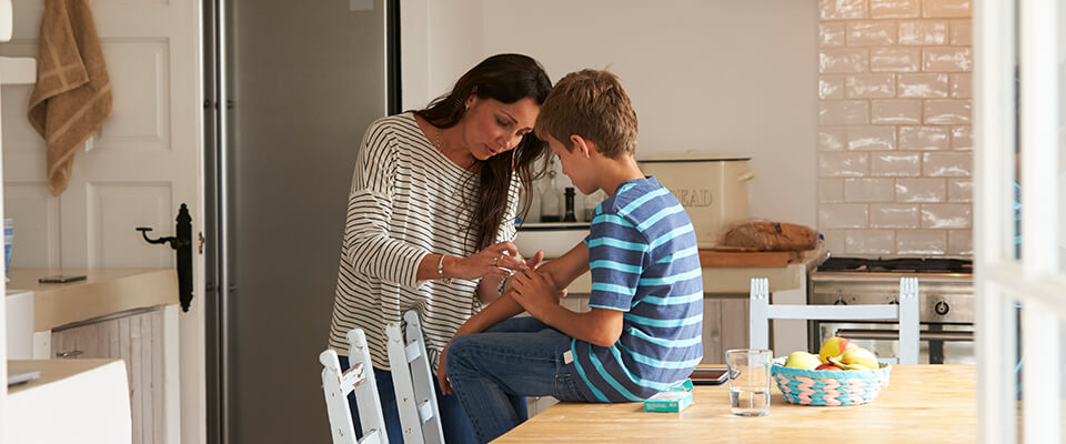 Mother putting plaster on sons arm