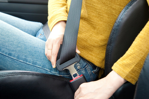 Woman putting her seatbelt on