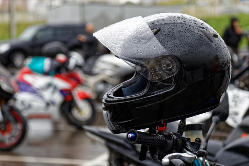 Wet motorbike helmet on handlebars