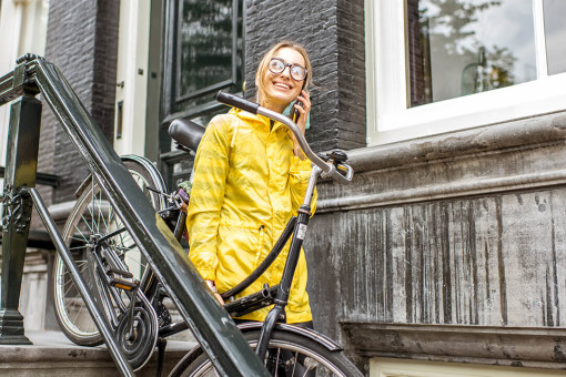 Woman holding her bike at the entrance to her house