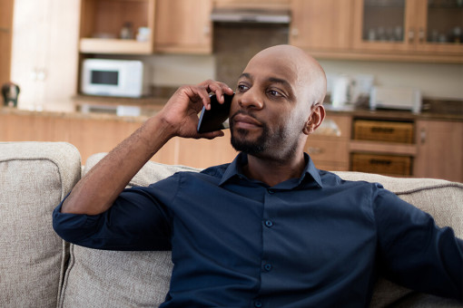 Man talking on phone in living room