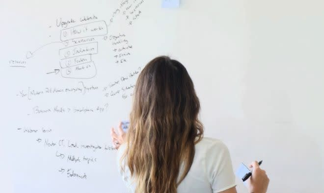 A stock image of a woman writing on a whiteboard