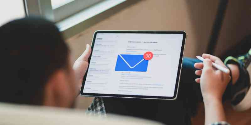 A man checks email on a tablet. An envelope icon shows 38 new messages.