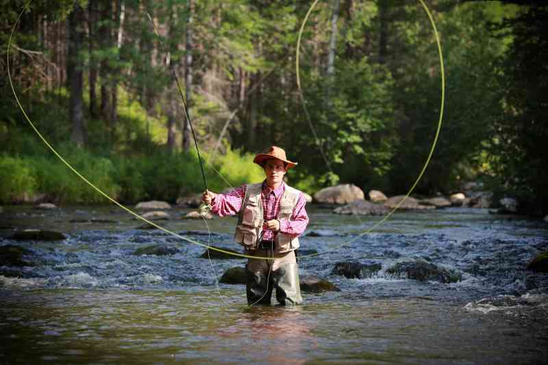 A man wears waders and a fishing vest as he stands in a river casting out his fly fishing line.