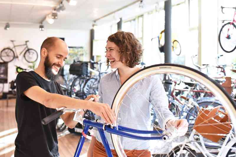 A man works on a bicycle in a bike shop while talking with a smiling customer.