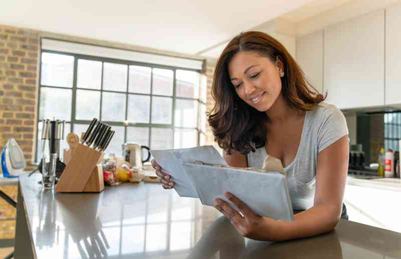 A woman in a kitchen reading the mail