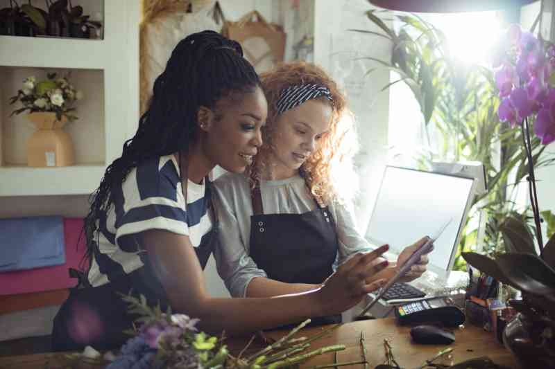 Two women in a flower shop looking at a tablet and computer.