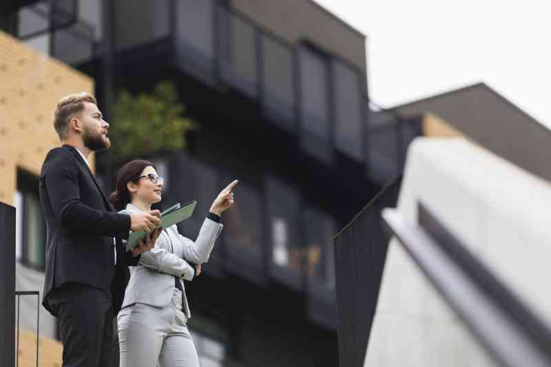 A man and woman stand outside looking at properties. He is carrying a folder and she is pointing up at a building.