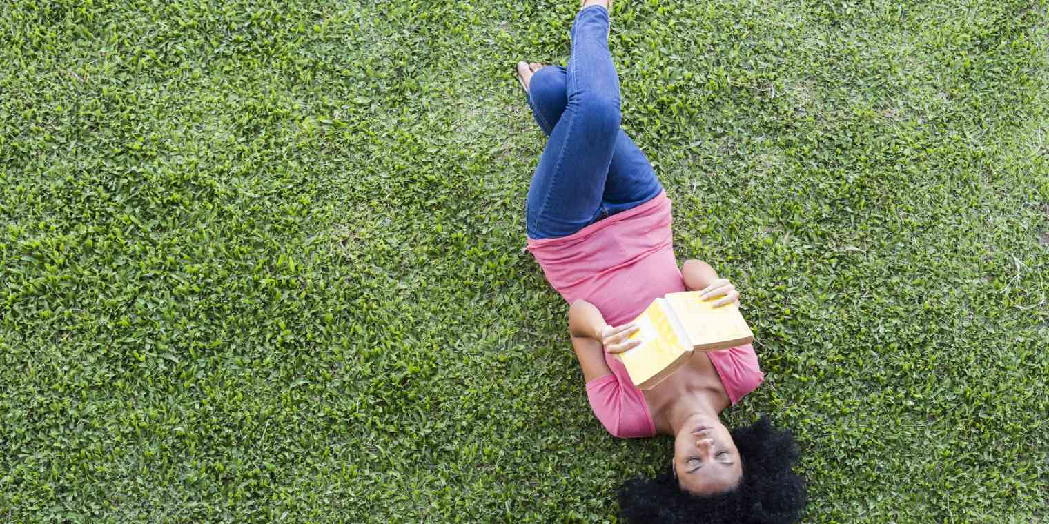 A woman wearing casual clothes lies on her back on a green lawn. She is reading a book.