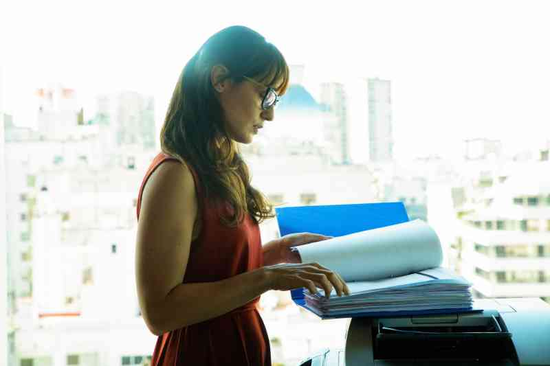 A woman at a copier with a large file.