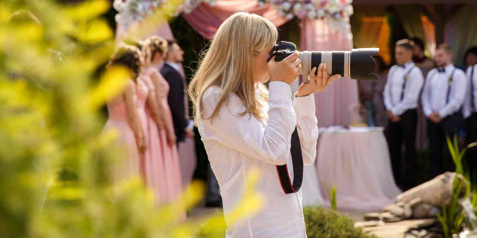 A woman wearing a white shirt holds a camera with a long lens up to her face. Out of focus in the background is a wedding party and a flowered canopy.
