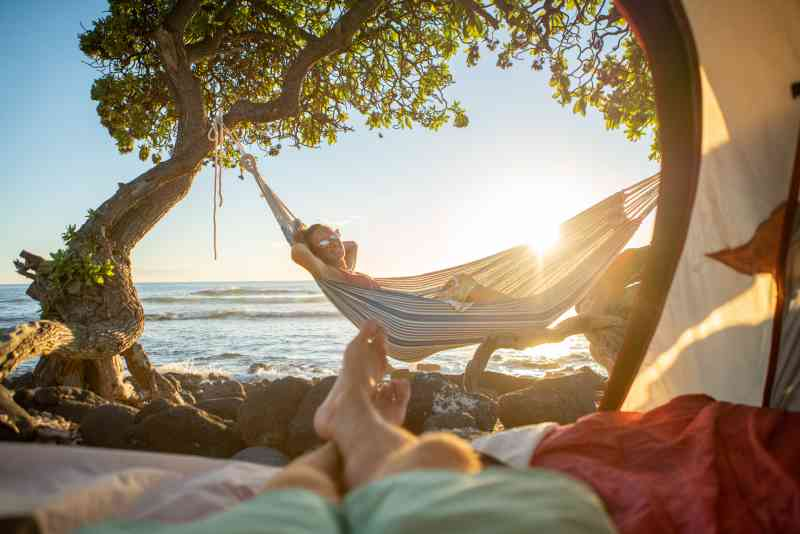 This photo is taken from the perspective of someone lying on the ground inside a tent, looking through the opening. In the foreground, you can see their legs, crossed at the ankle. They are looking at a woman relaxing in a hammock next to water.