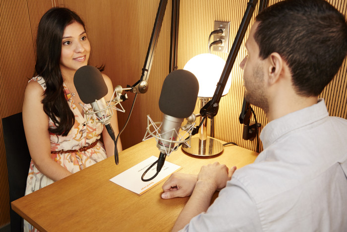 An interview between a woman and a man, both sitting at a desk with microphones.